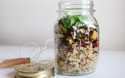 Farro e miglio con pomodori, zucchine e semi di girasole nel barattolo