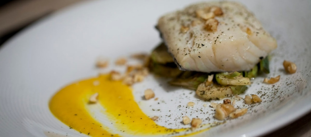 Baccalà con salsa di carote, carciofi, noci e polvere di rosmarino
